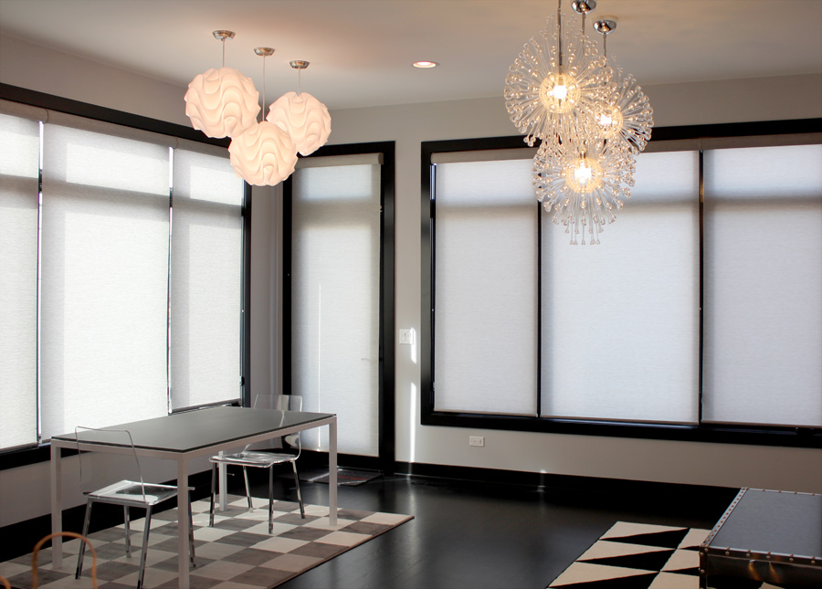 large windows with gray roller shades and dark trim with chandeliers in Chicago IL