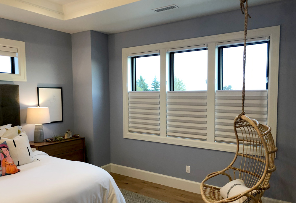 master bedroom with three windows covered with fabric roman shades in Chicago IL
