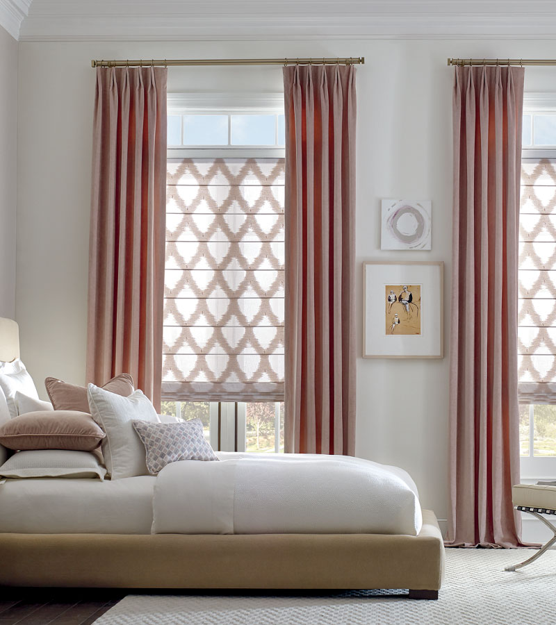 Blush pink drapery panels with gold rod and patterned fabric roman shades Vancouver WA