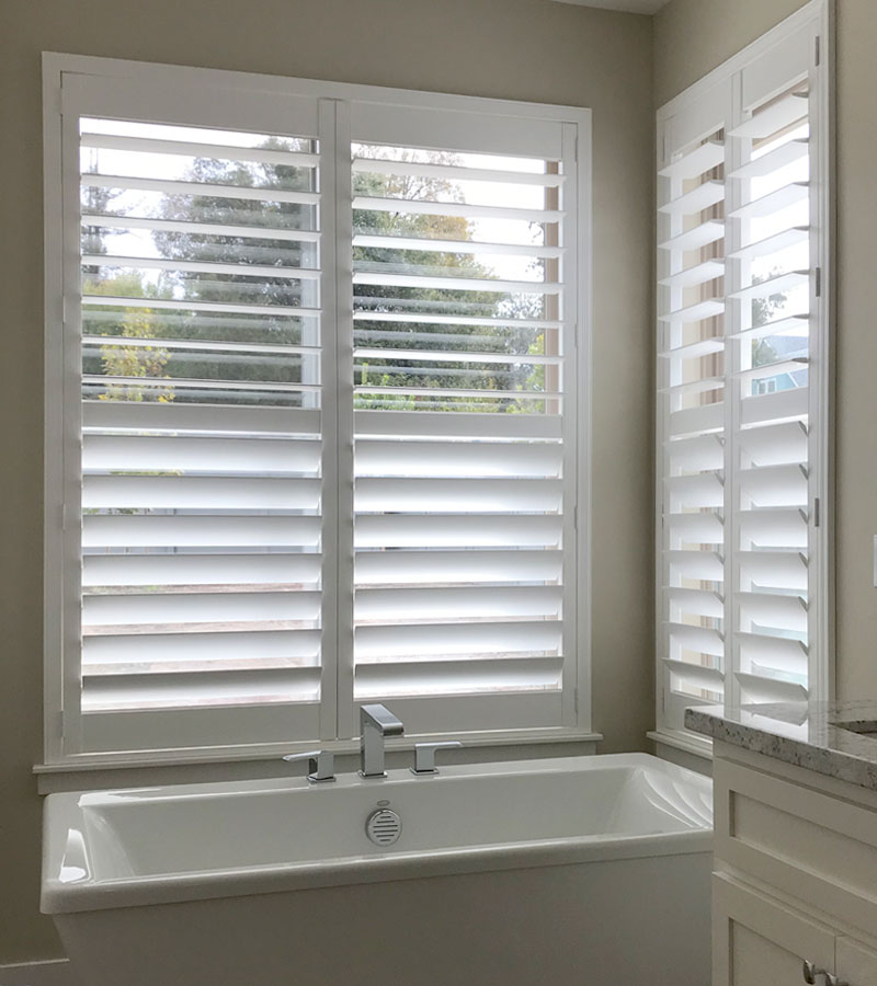 window treatments that save energy white plantation shutters in corner of bathroom in Naperville IL home