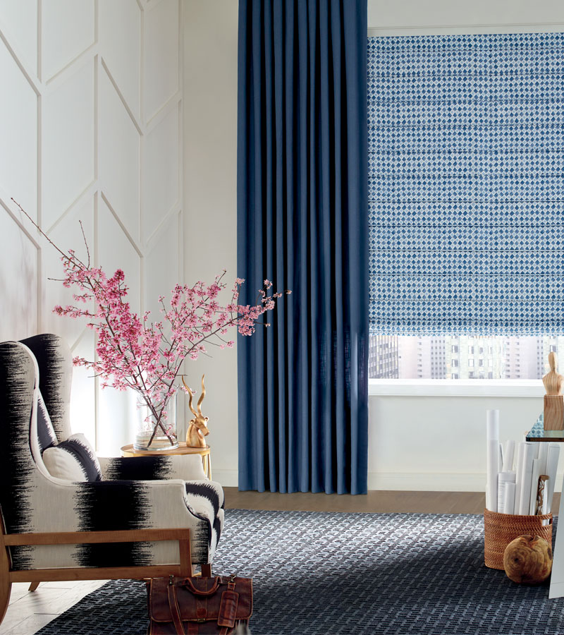 insulating window treatments with patterned blue roman shades and side draperies in Chicago 60611