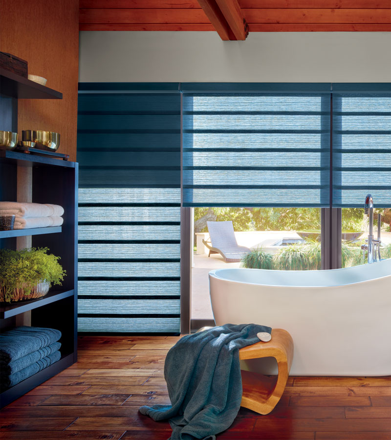 exterior wall of bathroom window with blue modern roman shades in Beaverton OR
