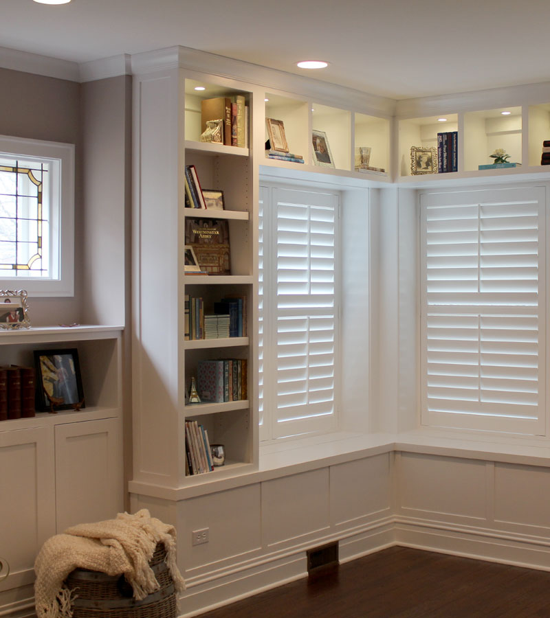 corner of living room with built-in shelves and windows with interior shutters in Hinsdale IL