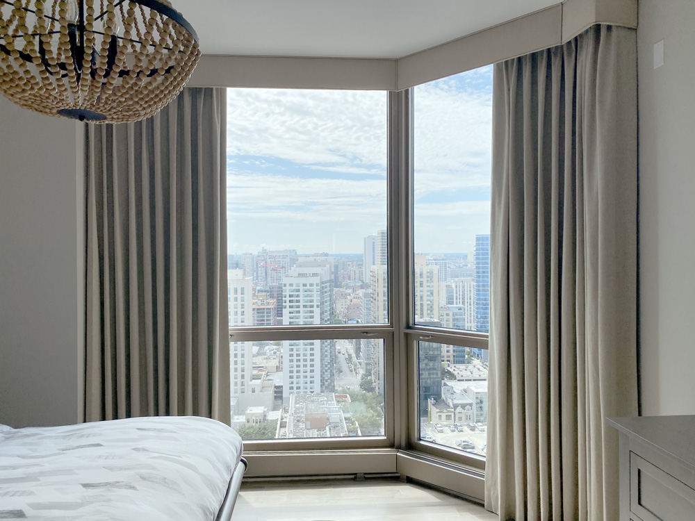 neutral roller shades layered with beige draperies in Chicago Gold Coast condo