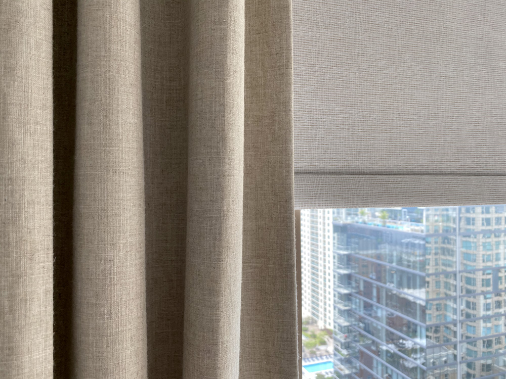close up neutral roller shades layered with beige draperies in Chicago Gold Coast condo