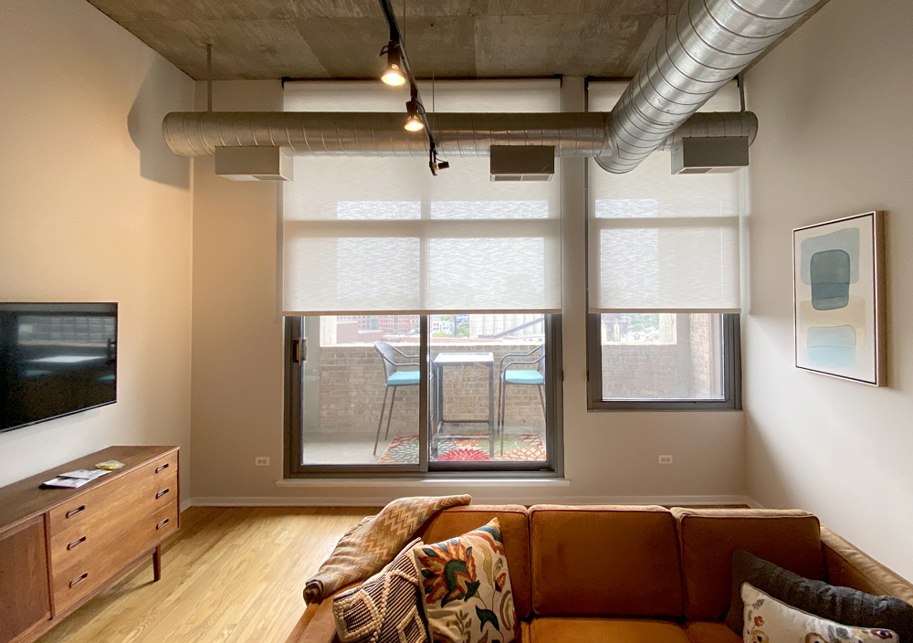 urban studio with beige roller shades on sliding doors Chicago IL