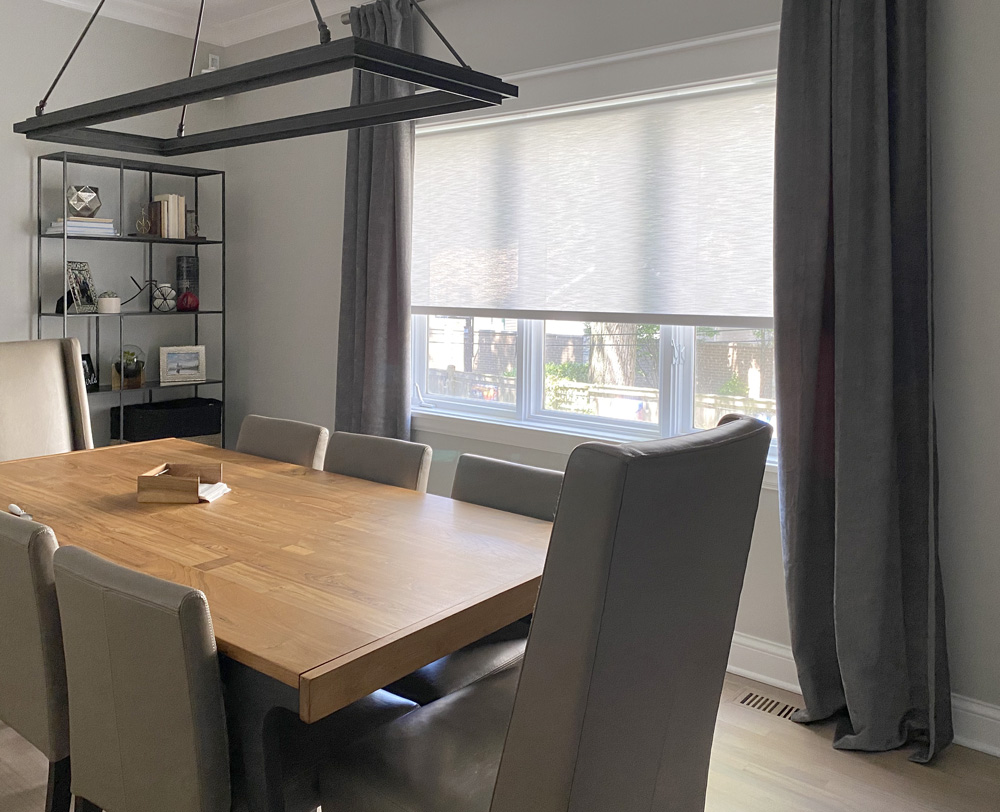 dining room with side drapery panels and light gray roller shade in Chicago IL