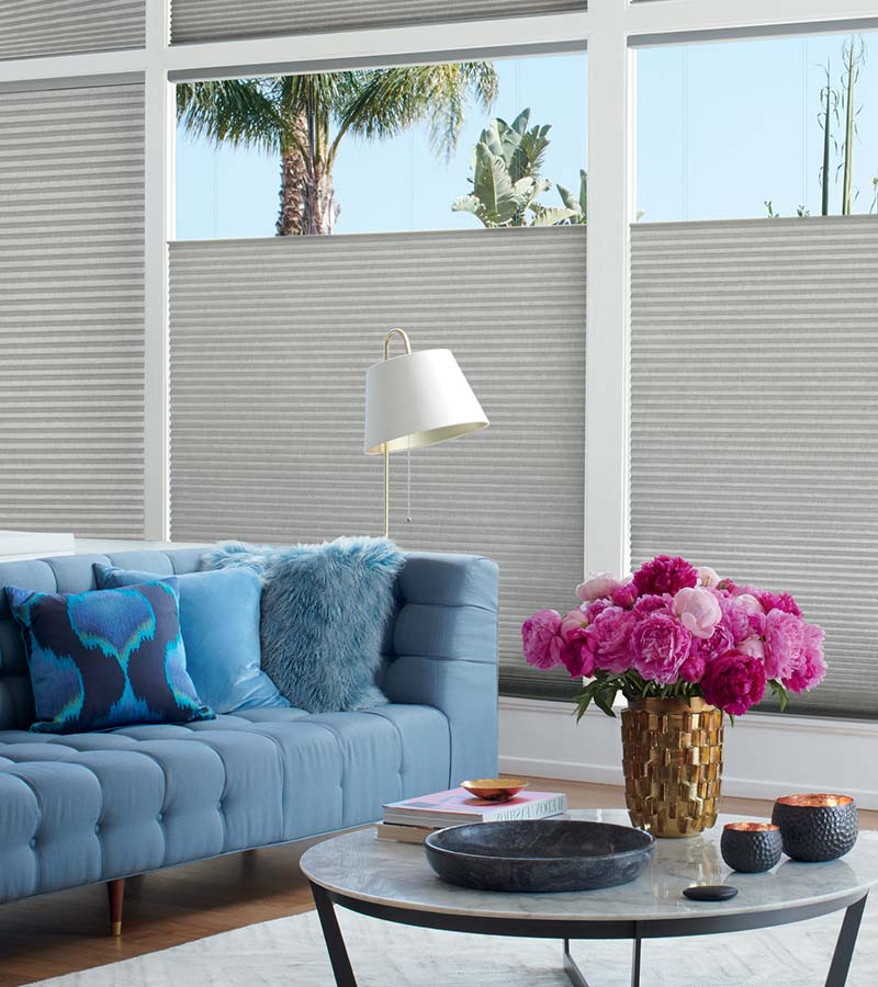 cellular blinds lowering from the top in living room with blue sofa in Portland OR