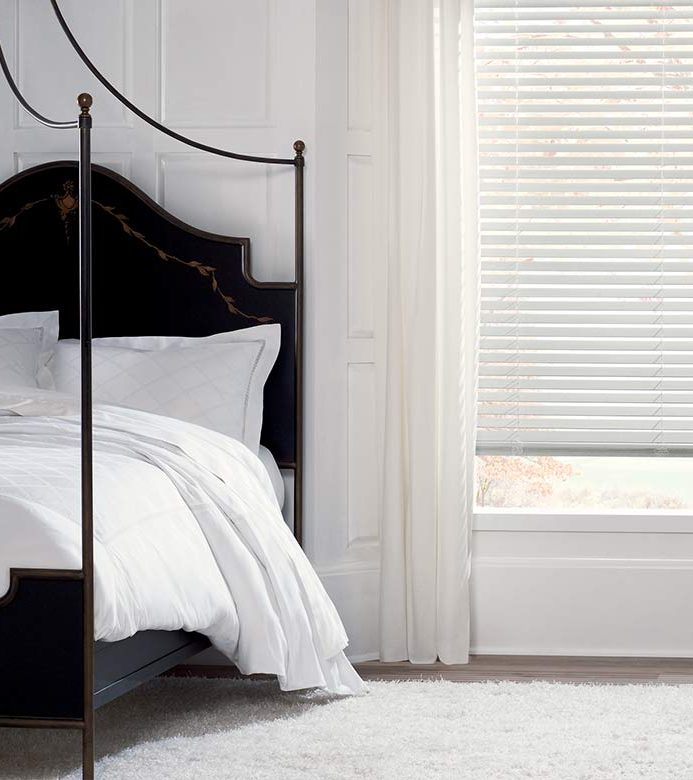 Minimalist white bedroom with white blinds with black bed frame in Portland, OR